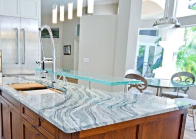 Thick Glass high bar over natural quartz countertop in Naples Florida with custom stainless  steel supports
