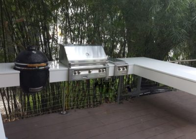 Floating Outdoor Kitchen with White Glass countertops  supported by custom steel structures by Matt Hall built for Thomas Everett Lamb in Tampa Bayshore home